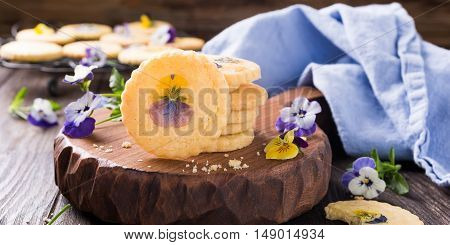 Homemade shortbread cookies with edible flowers on old wooden background. Holiday food