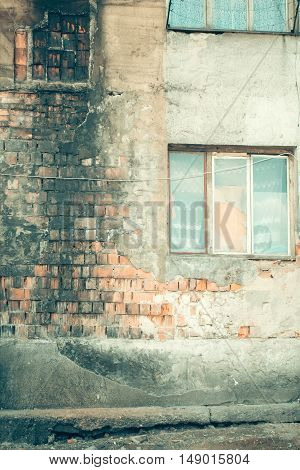 Old grunge house with burnt red brick walls cracked plaster cement windows on masonry background