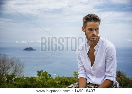 Handsome Young Man in Trendy Attire, n a Sunny Summer Day with Italian Sea Coast in the Distance, Wearing a White Shirt