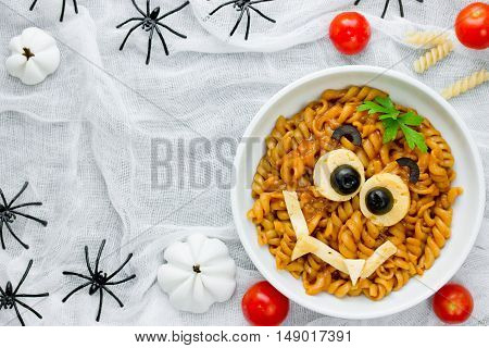 Pasta bolognese on Halloween party fun recipe for kids to dinner or lunch edible cute monster face from fusilli in sauce top view of empty space for text