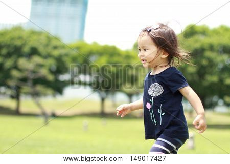 Japanese girl walking on the grass (1 year old)