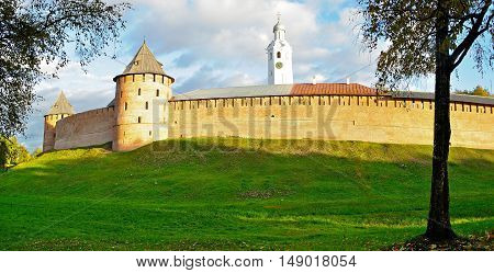 Architecture autumn colorful landscape - panorama of Veliky Novgorod Kremlin fortress and clock tower on the hill under warm autumn sunset light in Veliky Novgorod Russia