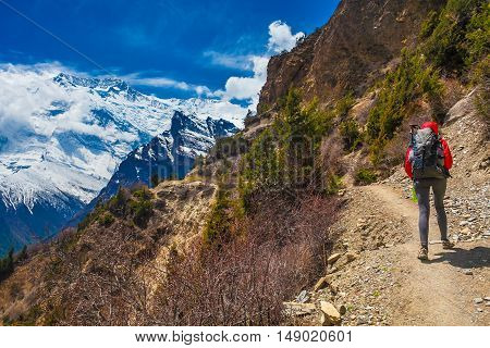 Young Pretty Woman Wearing Red Jacket Backpack Trail Mountains.Mountain Trekking Rocks Path. Snow Landscape View Background. Horizontal Photo