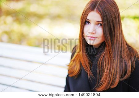 Portrait of a cute brown-eyed girl with her bright brown hair on a sunny day in autumn park.