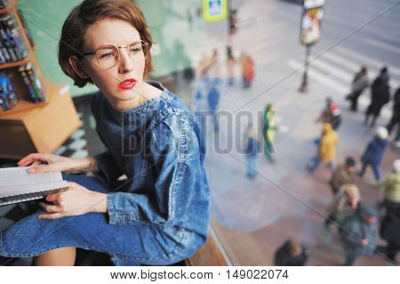Beautiful thoughtful girl in glasses and jeans dress in the library or in a bookstore sitting at the window holding an open book looking through the window into the street.