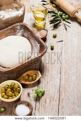 Various traditional ingredients for preparation of cooking of bread with olives on a old wooden background with copy space.