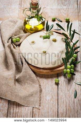 Yeast dough for olive bread decorated with branch of olive tree and olive oil on a rustic wooden background with copy space.