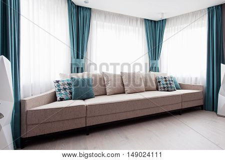 Large modern couch in the room near a big window light and turquoise tones