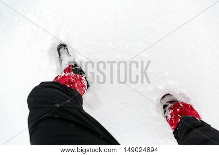 Shoes on snow in white winter forest during hiking. Legs and hiking boots on white snowy background. Travel recreation fitness and healthy lifestyle. Motivation and inspirational winter landscape.