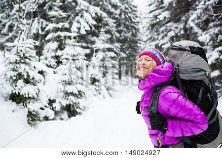 Happy young woman hiking in white winter forest woods with backpack. Girl walking on snowy trail. Inspirational travel and healthy lifestyle. Camping in snow winter landscape.