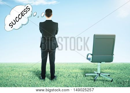 Back view of swivel chair and businessman on grass looking into the distance and thinking about success
