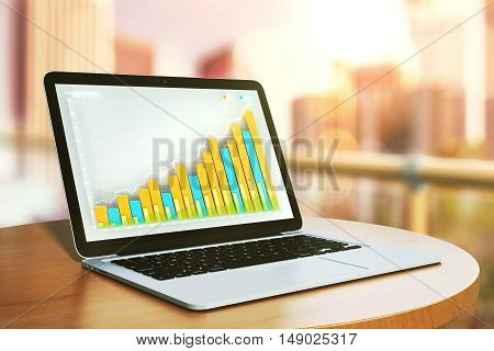 Closeup of laptop computer with colorful business graph placed on balcony table with blurry city view. Financial growth concept. 3D Rendering