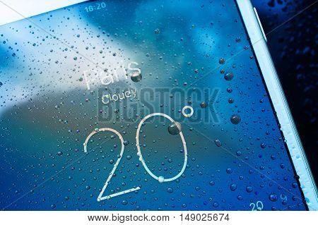PARIS FRANCE - SEP 26 2016: New Apple iPhone 7 Plus unboxing and testing - Paris weather forecast on screen covered with rain drops. New iPhone7 is one of the best waterproof smart phone in the world