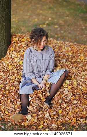 Beautiful romantic woman sitting near a tree on fallen leaves sunny autumn day