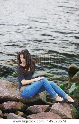 Young beautiful brunette girl with long hair sitting on the rocks by the sea on a background of dark green waves.
