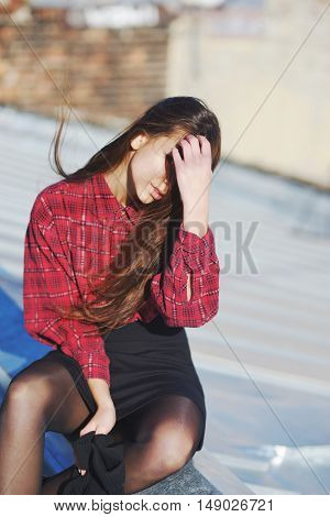 Young pretty girl sitting on the peak of the roof the wind ruffled her hair.