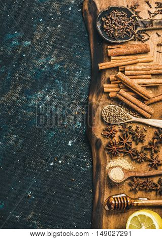 Ingredients for cooking mulled wine. Spices, honey, sugar and lemon on wooden board over old dark blue painted plywood background. Top view, copy space