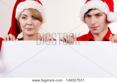 Couple holding banner sign with copy space for text peeking over edge of blank empty billboard. Happy glad girl and boy in santa claus hats. Christmas advertisement copyspace.