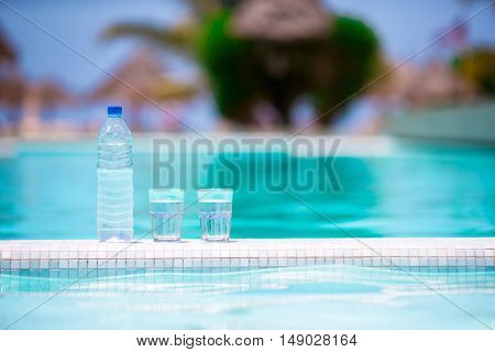 Glasses of waters and bottle on the edge of infinity swimming pool