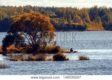 autumn landscape, tree and water in the distance a fisherman sitting and fishing, blue water and yellow vegetation, sunny day, clouds, sky, a man wearing a cap