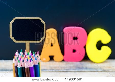Wooden Mini Blackboard Label And Colouring Pencils Over Chalkboard Background