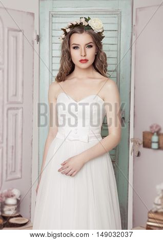 Beautiful young bride in wedding romantic decoration pink and green. Wooden boxes bottles and different wedding decoration