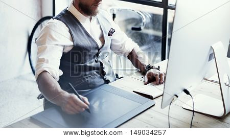 Closeup Bearded Graphic Designer Working Drawing Digital Tablet Desktop Computer Wood Table.Stylish Young Man Wearing Glasses White Shirt Waistcoat Work Modern Loft Creative Startup Project Blurred