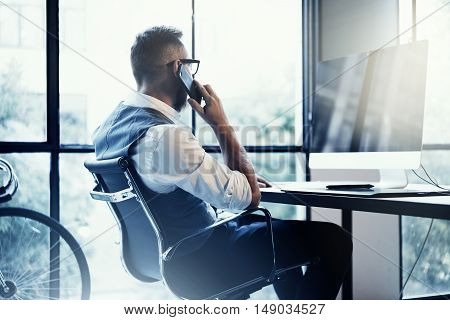 Stylish Bearded Young Man Wearing Glasses White Shirt Waistcoat Working Modern Loft Startup.Creative Guy Using Mobile Phone Call Partner.Person Work Drawing Tablet Desktop Computer Wood Table.Blurred