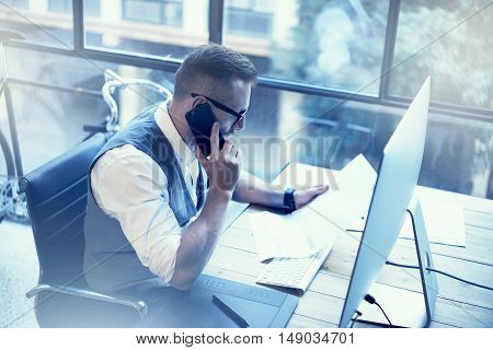 Bearded Businessman Making Great Business Decisions Modern Workplace.Young Man Working Startup Desktop.Using Smartphone Call Meeting Partner.Guy Wearing White Shirt Waistcoat Work Office.Blurred