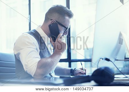 Bearded Businessman Making Great Business Idea Modern Workplace.Young Man Working Startup Desktop.Using Smartphone Call Meeting Partner.Guy Wearing White Shirt Waistcoat Work Office.Blurred