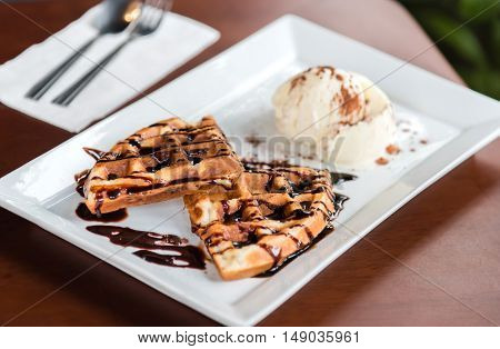 Waffle and chocolate serve with vanilla ice cream in white plate.