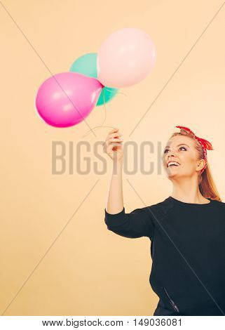 Happiness and carefree concept. Blonde smiling woman with colorful latex balloons flying balls. Retro fashion styled girl portrait.