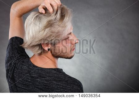 Handsome young fashion model with colored hair highlighted stylish haircut ear plug side view