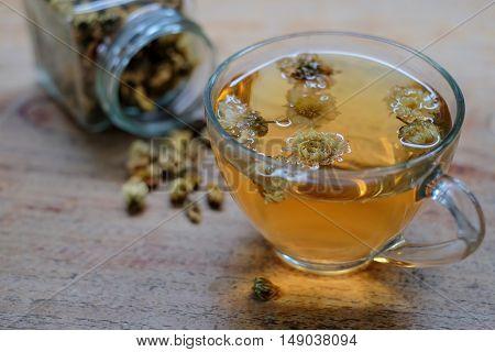 Chrysanthemum tea glass on a wooden floor.