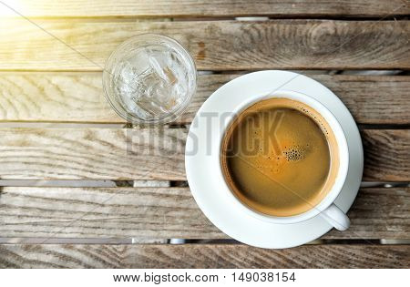white coffee cup and glass water on wooden table.Top view focus.
