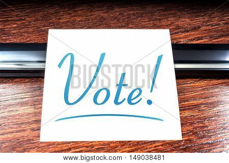 Vote Sticky Note On Paper Lying On Wooden Cupboard