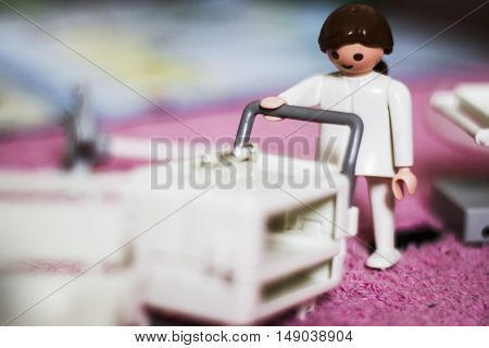 Doll dressed in white nurse pushing cart