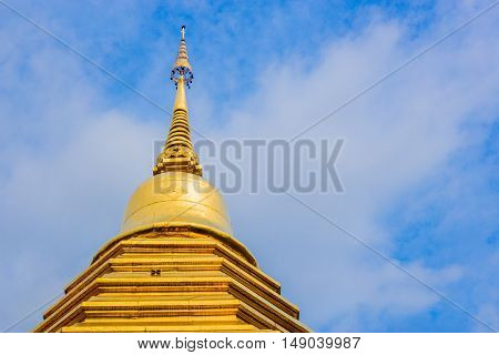Bangkok Thailand 07/09/2016 Top of a golden temple building on a sunny day with clouds and blue sky background in Bangkok Thailand