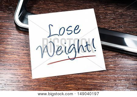 Lose Weight Reminder On Paper Lying On Wooden Cupboard