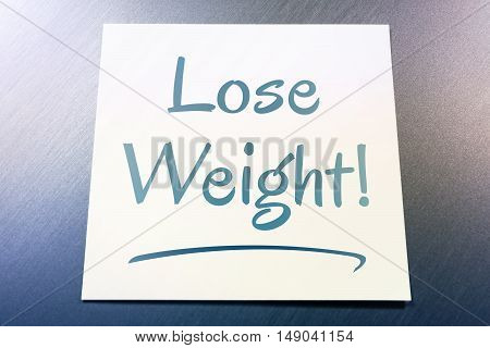 Lose Weight Reminder On Paper Lying On Brushed Aluminum Of Fridge