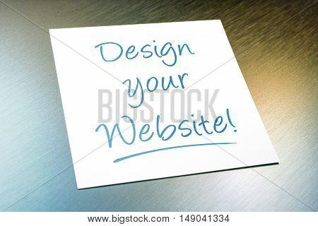 Design Your Website Paper Lying On Brushed Aluminum Of Refrigerator
