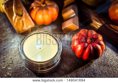 Halloween Decoration With One Candle Light, Chocolate And Pumpkins On Slate