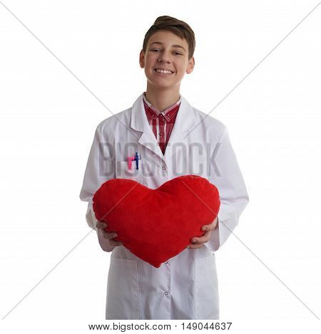 Cute teenager boy wearing white lab medic coat with red plush heart over white isolated background as science, medicine, healthcare concept