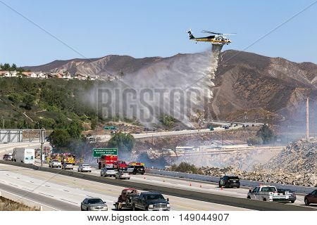 CANYON COUNTRY, CALIFORNIA - SEPTEMBER 25, 2016: The Los Angeles Fire Department helicopter drops fire retardant on a brush fire off the 14 freeway in Los Angeles County.