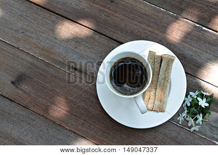 Good morning concept : Cup of coffee, fresh tuna sandwich and white flowers on wood background, breakfast with fresh tuna sandwich and coffee