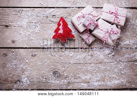 Wrapped christmas presents and decorative fur tree on aged wooden background. Selective focus. Top view. Place for text.