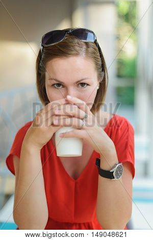 young woman in red dress drinking drink at cafe near window