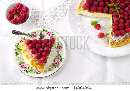 Cheesecake, souffle, cream mousse, pudding dessert with fresh raspberries and mint leaves on a white plate.