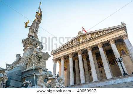 Austrian parliament building with Athena statue on the front in Vienna, Austria. Beautiful travel picture with sunset light.