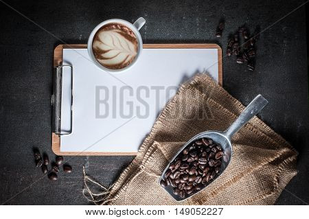 Blank clipboard with coffee bean on black stone background